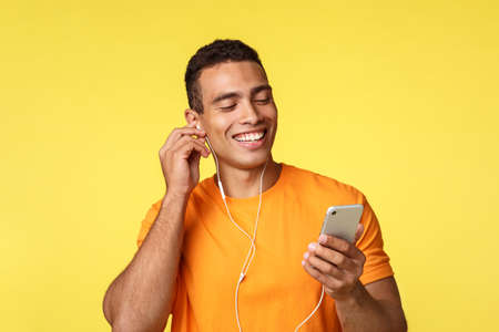 Cheerful smiling masculine young man in orange t-shirt, holding smartphone, chatting as listening music or watching video in headphones, got voice message and laughing over it, yellow background