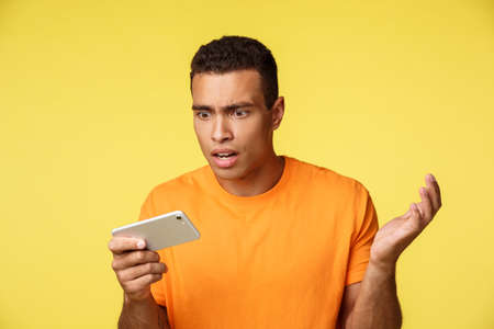 Shocked and bothered, upset handsome guy in orange t-sirt, stare at mobile screen questioned and sad, losing, see bad news, raise hands in dismay, read upsetting results, standing yellow background