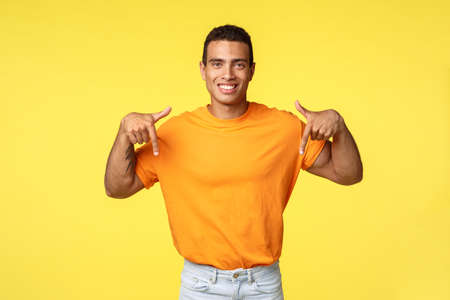 Good-looking young masculine man in orange t-shirt giving advice where buy online, pointing down smiling assertive and happy, promote advertisement, give recommendation, yellow background