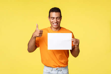 Happy handsome hispanic guy in orange t-shirt, hold blank paper, look at piece and smiling in approval, show thumb-up gesture, like promo, recommend visit company web page, yellow background