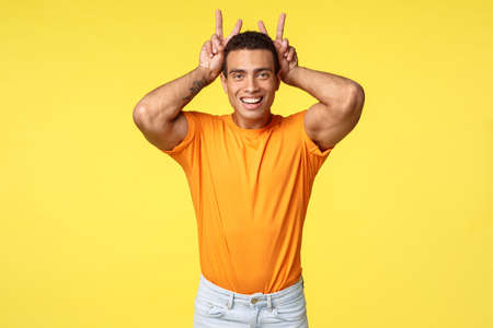 Cute masculine and silly hispanic boyfriend in orange t-shirt, make peace gesture, bunny ears behind head, smiling joyfully, mimick rabbit to fool around play with niece over yellow background 스톡 콘텐츠