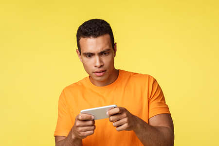 Focused and serious young handsome guy trying pass hard level, frowning and stare strict camera, carried-away with interesting tough game, holding smartphone horizontally, stand yellow background