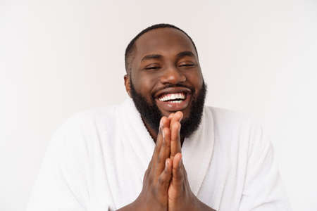 Black guy wearing a bathrobe pointing finger with surprise and happy emotion. Isolated over whtie background. Foto de archivo