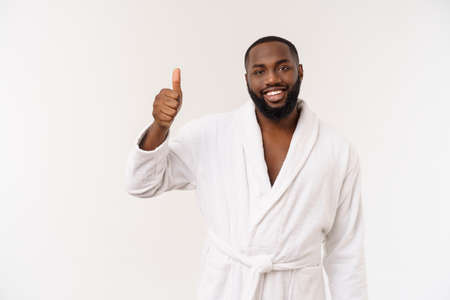 Black guy wearing a bathrobe pointing finger with surprise and happy emotion. Isolated over whtie background.