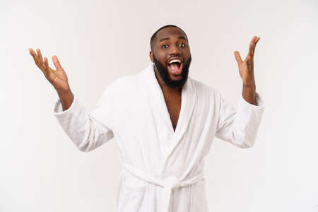 Black guy wearing a bathrobe pointing finger with surprise and happy emotion. Isolated over whtie background. Archivio Fotografico