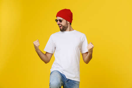 Successful young man celebrating against a yellow background.