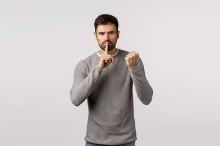 Shut up or else. Threatening angry and serious scary bearded man demand keep silent, dont tell anyone, threaten victim with shaking fist, press index finger to lips, untell, hushing, white background