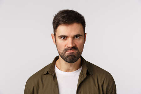Angry pissed bearded guy losing temper, want kill someone, staring aggressive, trying keep mouth shut and not hit person as feeling rage and aggression, suck lips, frowning staring with scorn