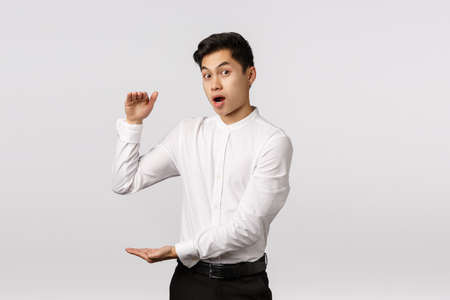 Curious and surprised handsome asian young guy consulting with coworker, gesturing as if holding something big, large box or vast object, open mouth impressed say wow, look camera astonished