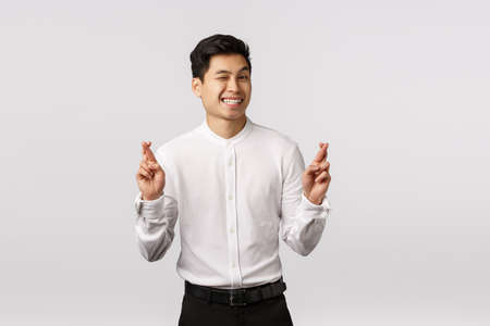 Cute hopeful optimistic asian male entrepreneur in white shirt, pants, wink camera cheeky, smiling assured everything be alright, cross fingers good luck, anticipate big deal at work signed Banque d'images