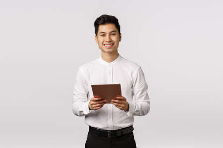 Cheerful, polite handsome elegant asian guy in white shirt, black pants, holding digital tablet and smiling camera, using gadget for work, messaging using device, shopping online, white background Foto de archivo