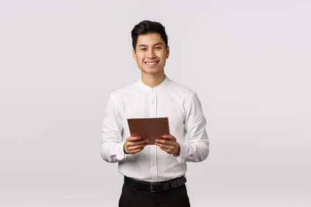 Wesoły, uprzejmy przystojny elegancki azjatycki facet w białej koszuli, czarnych spodniach, trzymający cyfrowy tablet i uśmiechniętą kamerę, używający gadżetu do pracy, wiadomości za pomocą urządzenia, zakupów online, białe tło Zdjęcie Seryjne