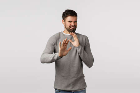 Eeew take it away from me. Disgusted and disappointed bearded man step back and defend himself raised hands, restrain from disgusting stinky product, cringe, feeling aversion and reluctance