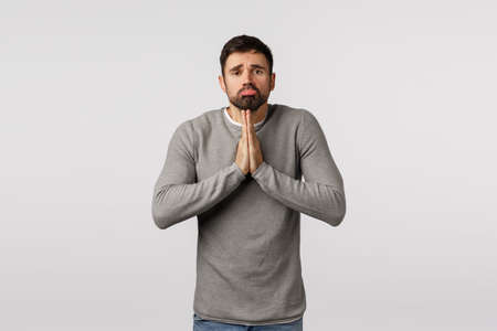 Clingy and cute bearded guy want something badly, make promise, pouting looking angelic tender expression asking help or mercy, hopefully press hands together pray, begging white background