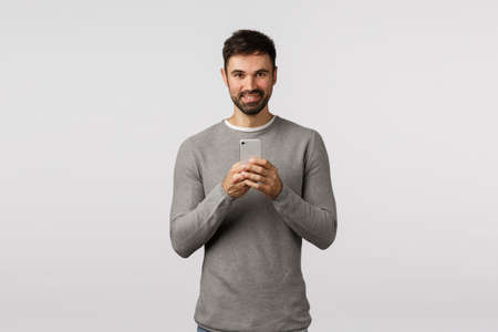 Handsome smiling and happy caucasian bearded man taking photo on smartphone, holding mobile phone near chest, grinning, photographing, record video, stream concert online, white background Stock fotó