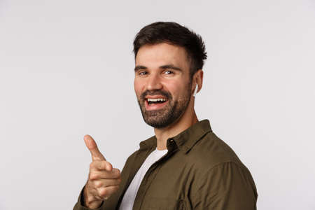 Hey it was nice talking you. Cheerful, handsome bearded modern guy standing profile, turn camera and smiling, pointing finger pistol gesture satisfied, listen music wireless headphones