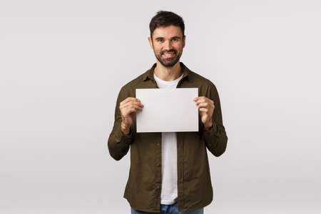 Assertive smiling cheerful bearded caucasian man in coat, holding blank paper near chest and grinning, searching for employees, have job or produce offer, place corporate banner, white background