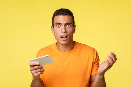 Shocked upset and questioned young man cant understand how he lost in game, stare camera puzzled, holding smartphone horizontally, raise arm in dismay and sadness, standing yellow background