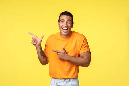 Cheerful excited man with tattooed arm in orange t-shirt, smiling astonished telling something amazing happened pointing left to promote exciting event, advice see yourself, yellow background