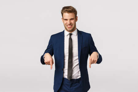 Guy turn your attention at something awful and unpleasant. Attractive blond bearded businessman in classic suit, pointing down and grimacing from aversion, seeing creepy thing, white background 版權商用圖片
