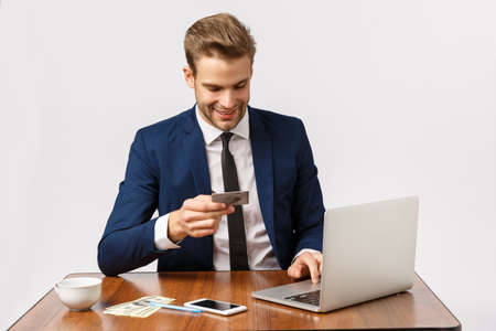 Handsome young businessman sitting office in suit, place online order, insert banking details shopping site via laptop, holding credit card, waiting for call as smartphone lying table with money