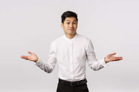 Cant help you sorry. Handsome asian businessman shrugging, spread hands sideways dismay and wonder, frowning and smirk awkward, dont know anything, clueless, unable to answer, white background