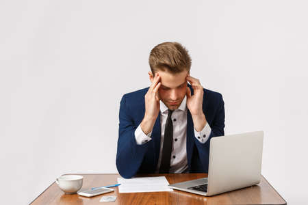 Failure, fatigue and depression concept. Man having bad day, feeling let down, losing important case in court, sitting office table with laptop and documents, touching temples, have headache Stock fotó