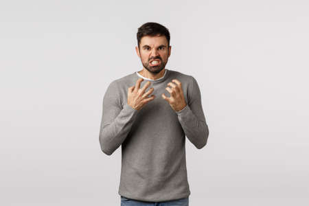 Guy hate everyone look with rage, hateful and furious expression, want choke someone, clench fists threatening, losing patience, look tensed and aggressive, grimacing annoyed, white background Stock Photo