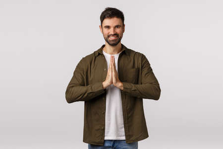 Cheerful, relaxed and friendly smiling caucasian man press palms together in pray, grinning, meditating or finish yoga practice, bowing to express gratitude sensei, standing white background Stock fotó