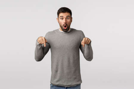 Surprised and speechless, excited handsome bearded guy feel emotional and impressed, folding lips in wow, amazement expression, pointing down, see stunning promo, want to try, show friends