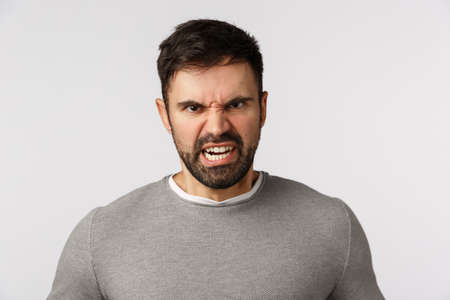 Rage, aggression and hate concept. Outraged and furious bearded adult man frowning, grimacing stare bothered and disgusted, express scorn or disdain, cursing someone want fight, white background