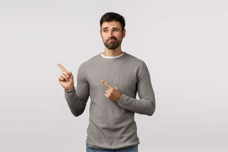 Lame, not good. Displeased and hesitant gloomy, grumpy cute bearded man, shopping in store see something doubtful with skeptical, unsatisfied expression, pointing looking left, smirk unimpressed