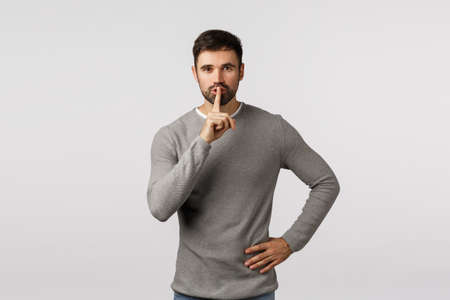 Shhh, its secret. dont tell anyone. Mysterious charming and kind young bearded dad asking keep quiet, shushing with index finger pressed to lips, seal mouth, tell be silent, white background