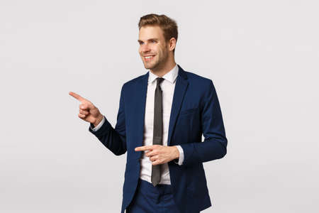 Cheeky, confident rich and successful male entrepreneur, caucasian blond man in classic suit, pointing and looking left, smiling pleased, seeing wonderful product, exactly what looking for