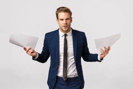 What is this, awful writing. Outraged and pissed handsome young blond bearded male entrepreneur, boss scolding employee with awful documentation, holding papers and looking distressed