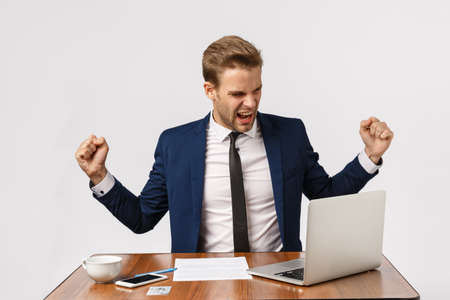 Relish, success and celebration concept. Cheerful good-looking boss, celebrating good news, do champion dance waving hands pleased, triumphing, looking laptop smiling, winning bid