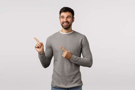 Pleased charming lucky young handsome male, adult in grey sweater, pointing looking left, observe cute scene, picked variant, see nice choice, happy and charmed, smiling satisfied