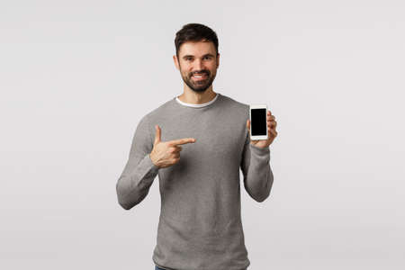 Handsome assertive and pleasant male with beard in grey sweater, promote application, filter app, devices, pointing smartphone display and smiling delighted, made right choice, white background