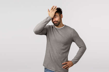 So dumb. Forgetful and displeased, tired bearded man in grey sweater, facepalm, punch forehead as forgot important task, hear lame stupid idea, smirk annoyed, standing embarrassed white background