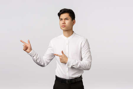 Sulking, displeased and angry young asian guy seeing his girlfriend flirting some other guy, frowning bothered, pointing looking left with disapproval and dislike emotion, white background
