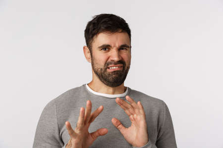 Eeew no thanks. Disgusted and displeased bearded guy grimacing, smirk and move away from disgusting thing, shake hands and step back frowning, express aversion, rejecting or refuse, white background