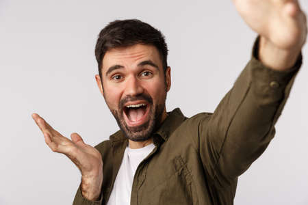 Happy and cheerful, glad young man introduce something as talking on online record video and describe product, hold smartphone extended arm, taking selfie, pointing left, white background Banque d'images - 135474196
