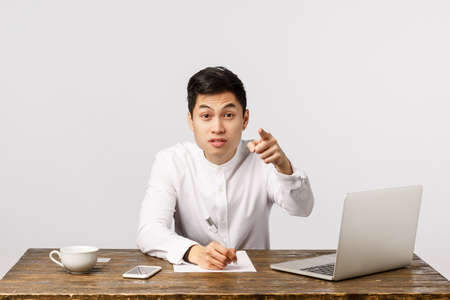 Get out. Serious-looking pissed boss writing down notes with pen on paper, pointing camera and staring strict, demand leave office dont disturb during work, sit office with laptop, smartphone