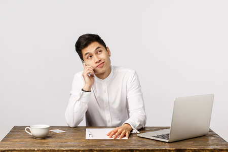 Reluctant good-looking chinese male entrepreneur in white shirt, sitting table in office with laptop, report documents and coffee cup, smirk unsatisfied, talking phone about something unpleasant Stock Photo
