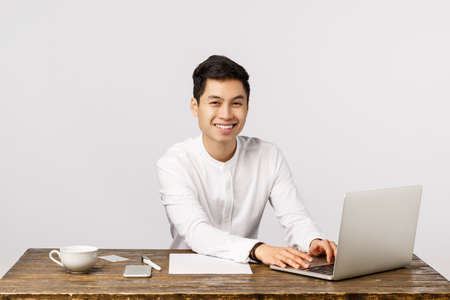Clients, company and finance concept. Happy cheerful asian man applied for job, sitting office desk and working laptop, smiling camera, found perfect corporation, become employee, white background