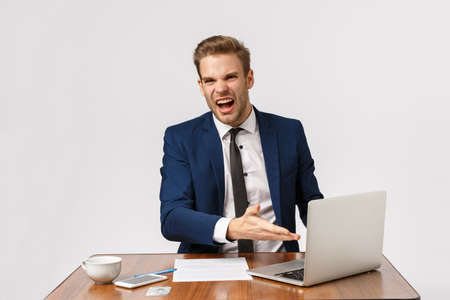 What the hell is that, its really bad. Bothered, outraged young boss, businessman in formal suit, sitting office desk, pointing laptop display complaining diagram, standing white background Фото со стока
