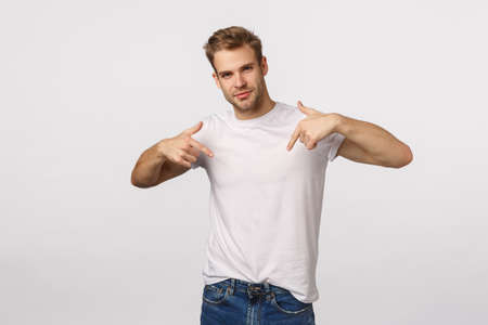 I am all you need. Handsome, assertive male model promote himself, pointing chest and smiling self-assured, want participate, suggest own candidature, standing white background Stockfoto