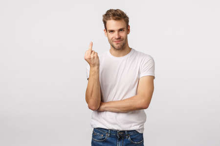 You know what, fuck you. Pissed handsome blond aggressive and rude guy with bristle, showing middle finger, smirk and look camera, telling opponent get lost, having argument, showing bad temper 版權商用圖片