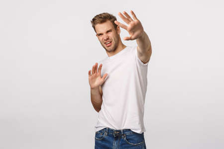 Turn-off that light. Displeased and bothered young handsome man defending himself trying cover something bright with raised hands, squinting discomfort, grimacing, famous person avoiding paparazzi