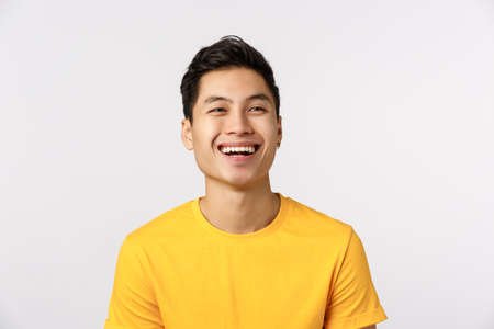 Friendship, joy and happiness concept. Cheerful young asian man in yellow t-shirt, look away as contemplate something beautiful, enjoy funny comedy movie on tv, smiling delighted, white background